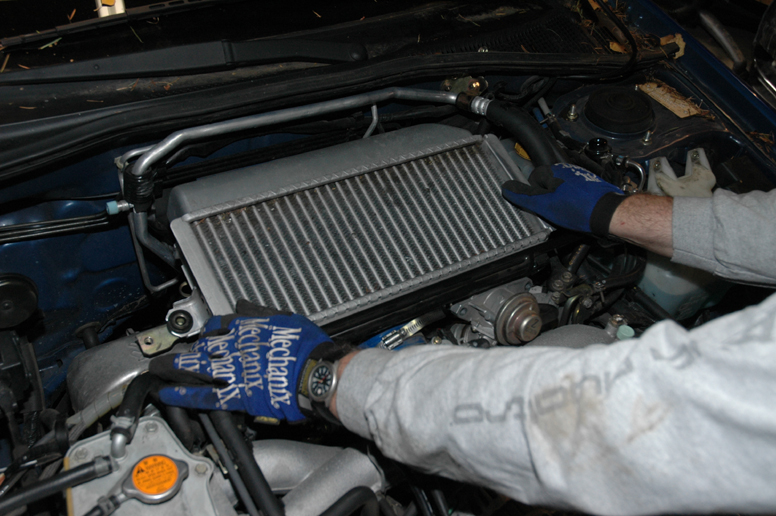 Carefully lift out the intercooler and the hoses should come free if you've loosened the clamps.